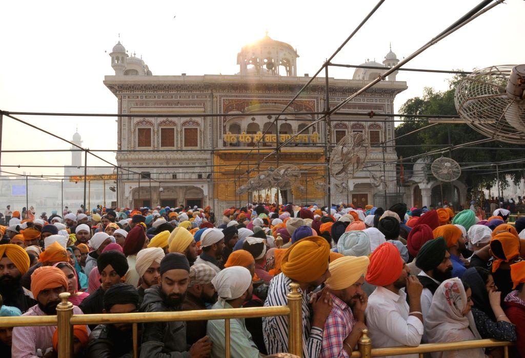 Sikh devotees throng the Golden Temple on during the 550th birth anniversary celebrations of Guru Nanak Dev in Amritsar on Nov 12, 2019. - Nanak Dev