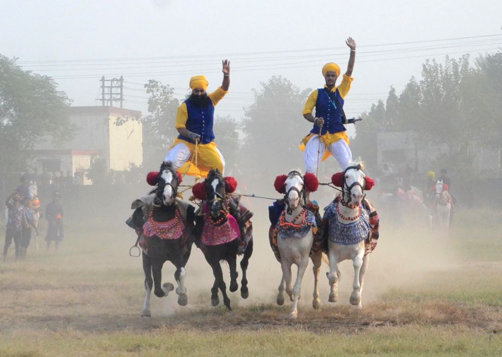Sikh 'Nihangs' show their horse riding skills during a religious procession organised on 'Fateh Divas' that marks the victory of the Sikhs against the Mughal Empire in Delhi in 1783, under ... - Baghel Singh
