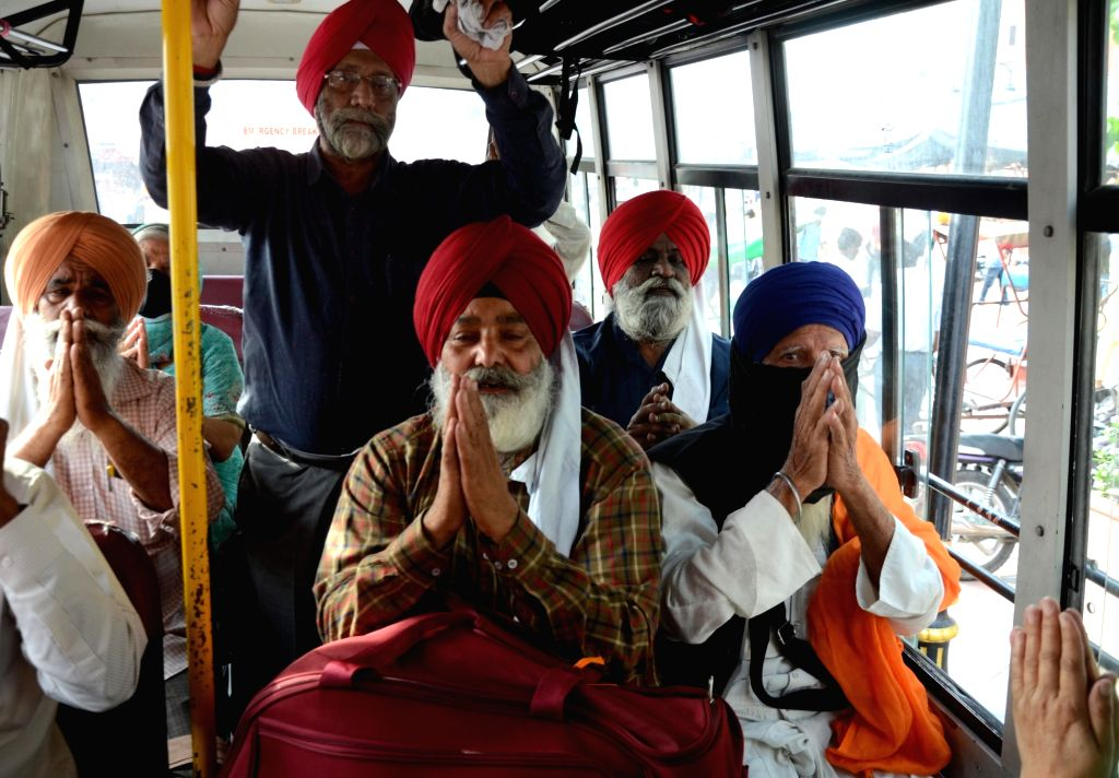 Sikh pilgrim sit on a bus and gesture as they leave for Pakistan for Baisakhi celebrations, in Amritsar on Monday, April 12th, 2021.(photo:Pawan sharma,/IANS)