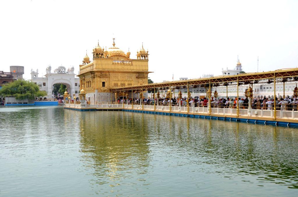 Sikh volunteers distribute sweet water on the occasion of the 415th Sikh Guru Arjan Dev's martyrdom day at the Golden Temple in Amritsar on Monday 14 June,2021. - Guru Arjan Dev