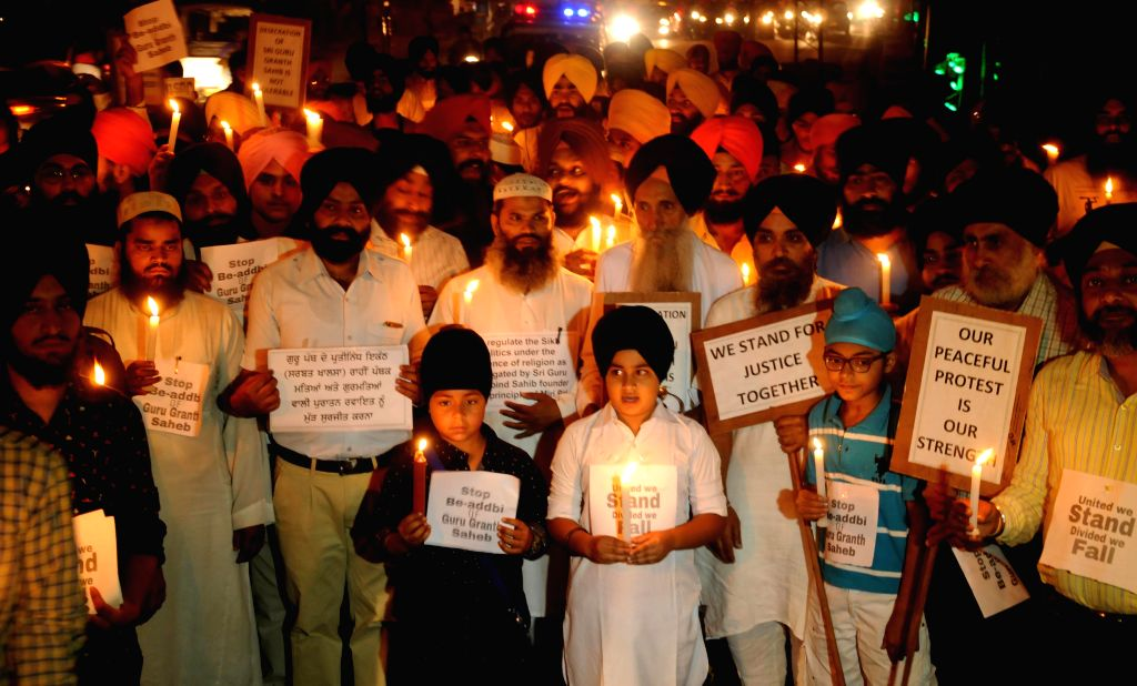 Sikhs hold a candlelight vigil to protest against desecration of the Sri Guru Granth Sahib in Amritsar, on Oct 21, 2015.