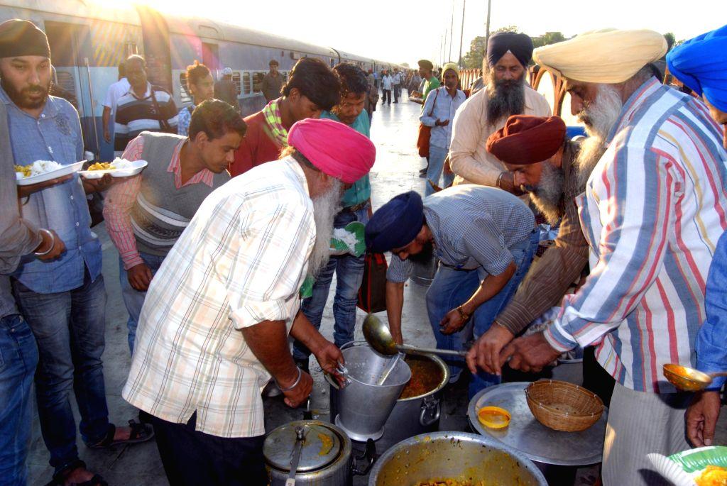 Sikhs organise a Langar for people returning back after observing Martyrdom Day of Guru Tegh Bahadur at Kamakhaya Railway station in Guwahati on Dec.8, 2013.