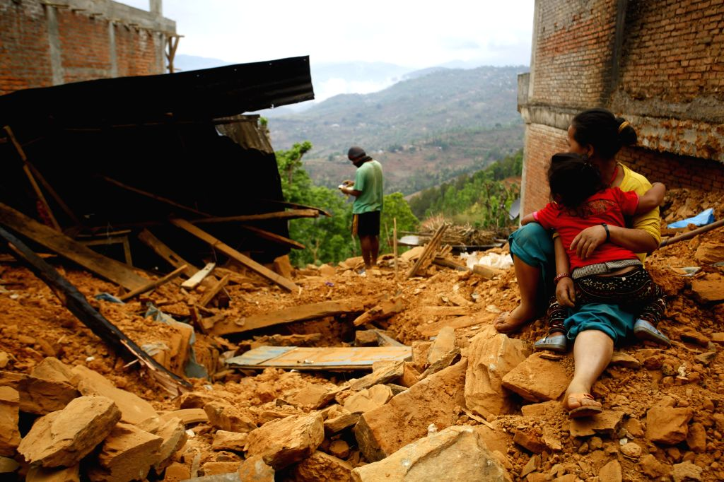 A woman and her child sit on the debris of her home after earthquake at Sindhupalchowk district, Nepal, April 29, 2015. By noon on Wednesday, more than ...