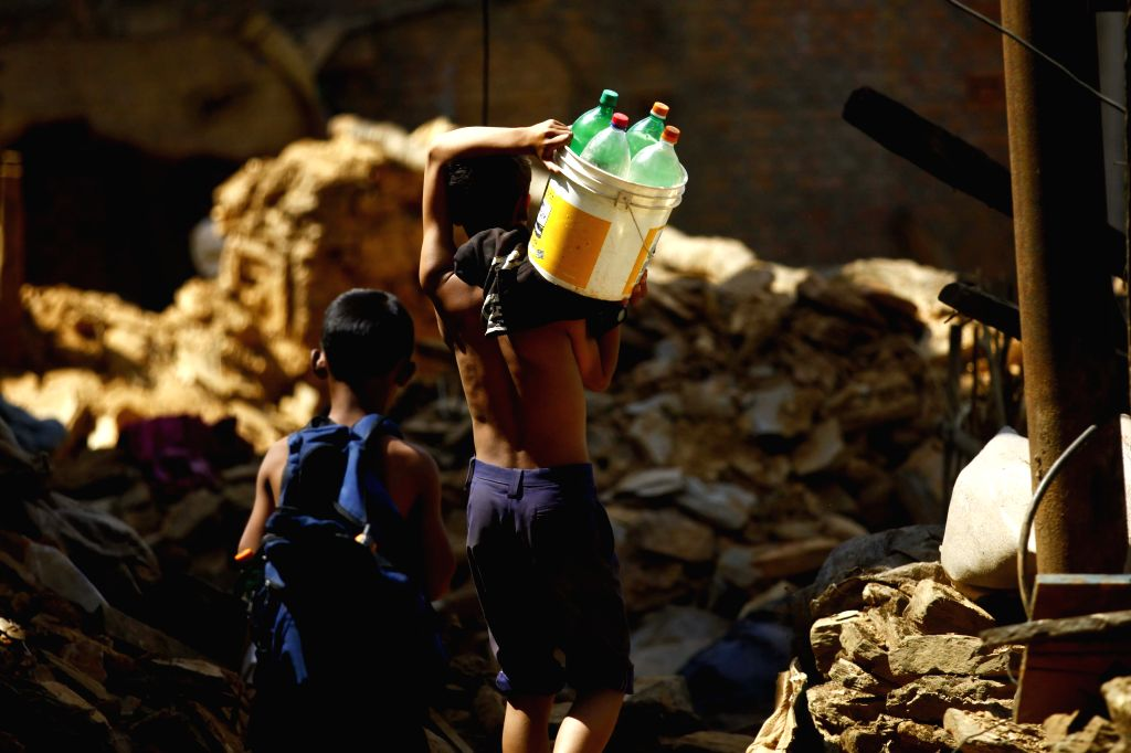 Boys carry bottles of water far from their houses after an earthquake in Sindhupalchowk, Nepal, May 3, 2015. At least 7,040 persons were confirmed dead with ...