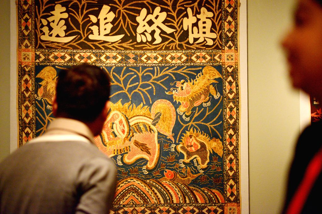 """Journalists view items on display during the preview of the exhibition """"Auspicious Designs: Batik for Peranakan Altars"""" at Peranakan Museum in ..."""