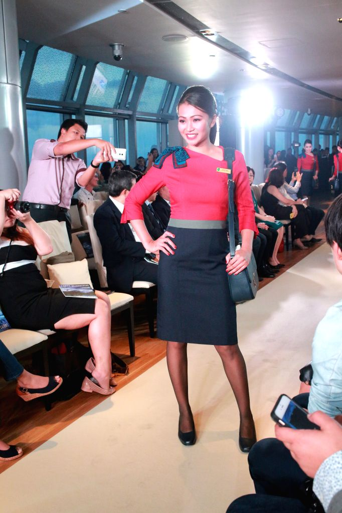 A stewardess displays a new uniform in Singapore, April 10, 2015. SilkAir, a regional unit of Singapore Airlines, launched a new collection of uniforms for its ...