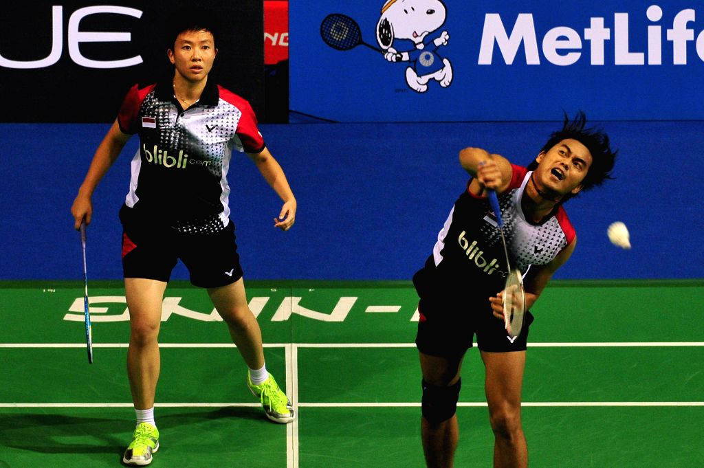 Tontowi Ahmad (R) and Liliyana Natsir of Indonesia compete during the mixed doubles semi-final match at the OUE Singapore Open badminton tournament against Liu ..
