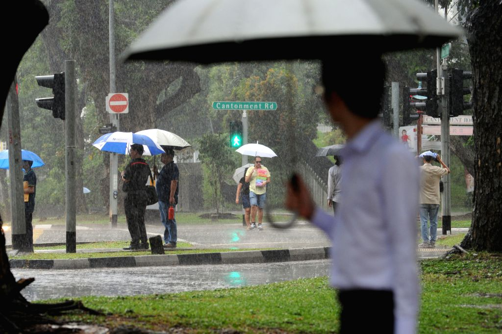 SINGAPORE, April 20, 2016 - People shelter themselves with umbrellas during heavy downpour in Singapore's city center, April 20, 2016. An afternoon downpour in Singapore on Wednesday helped to temper ...