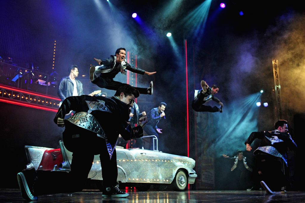 """Performers perform in the musical """"Grease"""" during a media call in Singapore's Marina Bay Sands Theatre on April 25, 2014. The musical ..."""