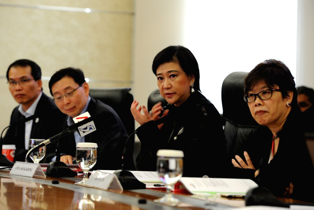 Group Chief Executive Officer of Singapore Telecommunications (SingTel) Chua Sock Koong (2nd R) attends a press conference in Singapore, April 8, 2015. SingTel on ...