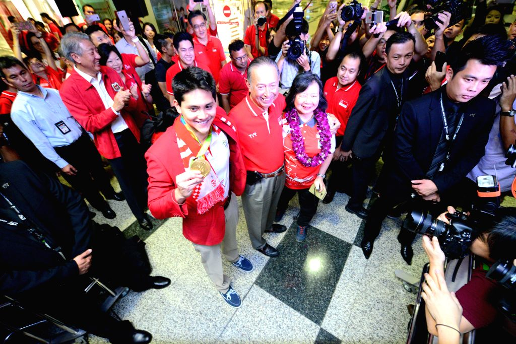 SINGAPORE, Aug. 15, 2016 - Singapore's gold medalist Joseph Schooling (L, front) poses for photos with his parents at Singapore's Changi Airport, Aug. 15, 2016. Singapore's first ever Olympic gold ...