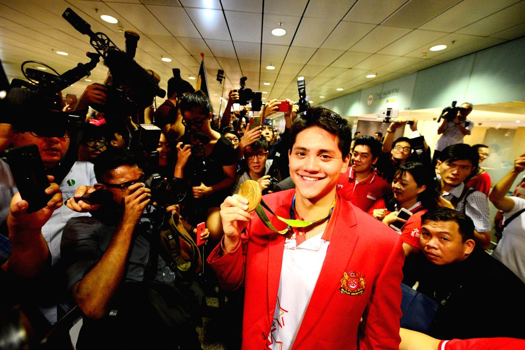SINGAPORE, Aug. 15, 2016 - Singapore's gold medalist Joseph Schooling (C) poses for a photo holding up his gold medal at Singapore's Changi Airport, Aug. 15, 2016. Singapore's first ever Olympic gold ...