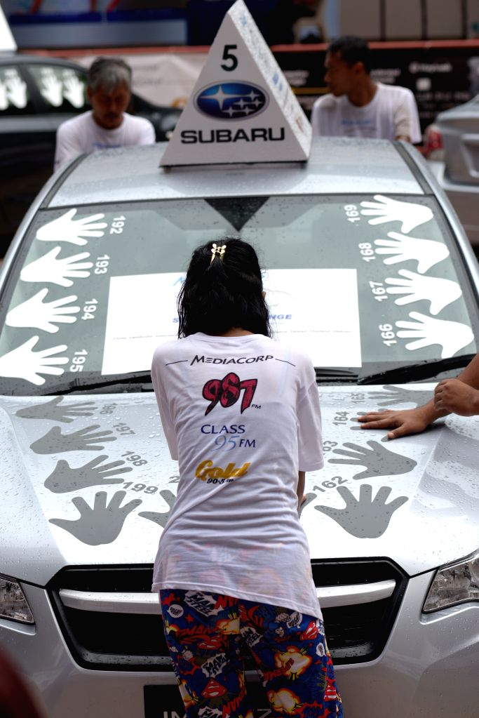Singapore : Contestants brave the elements during the Subaru Challenge held at Ngee Ann City Plaza in Singapore's Orchard Road on Nov. 11, 2014. The Subaru Challenge held in Singapore's Ngee Ann City