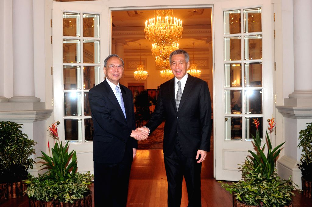 Singapore's Prime Minister Lee Hsien Loong (R) shakes hands with China's former Vice Premier Zeng Peiyan at Singapore's Istana, July 17, 2014.