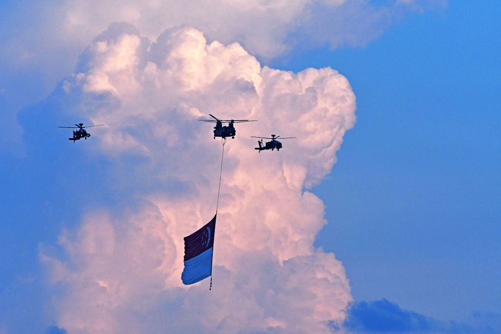SINGAPORE, July 27, 2019 - A helicopter of the Republic of Singapore Air Force tows a huge Singapore's national flag during the national day parade rehearsal held in Singapore, July 27, 2019. ...