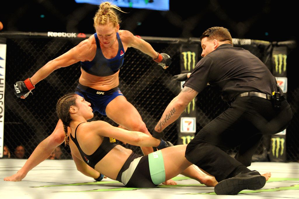 SINGAPORE, June 17, 2017 - Holly Holm (Top) of the United States knocks down Bethe Correia of Brazil during the women's bantamweight bout at the UFC Fight Night held in Singapore Indoor Stadium on ...
