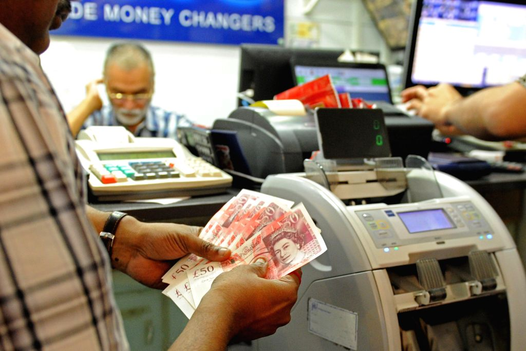 SINGAPORE, June 24, 2016 - A money changer counts British pounds in Singapore's Raffles Place, June 24, 2016. Britain's vote to leave the European Union (EU) resulted in the decline in value of the ...