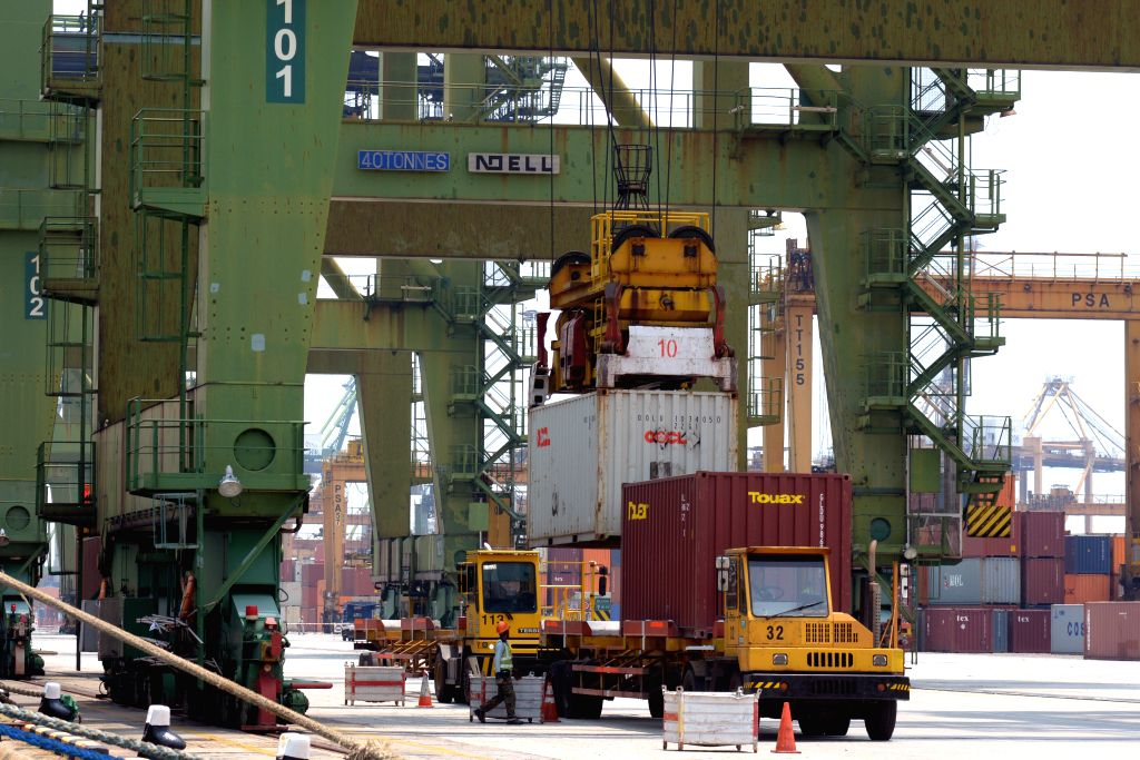 Photo taken on March 17, 2015 shows a cargo ship offloading containers at Singapore's Tanjong Pagar Container Terminal. Singapore's non-oil domestic exports ...