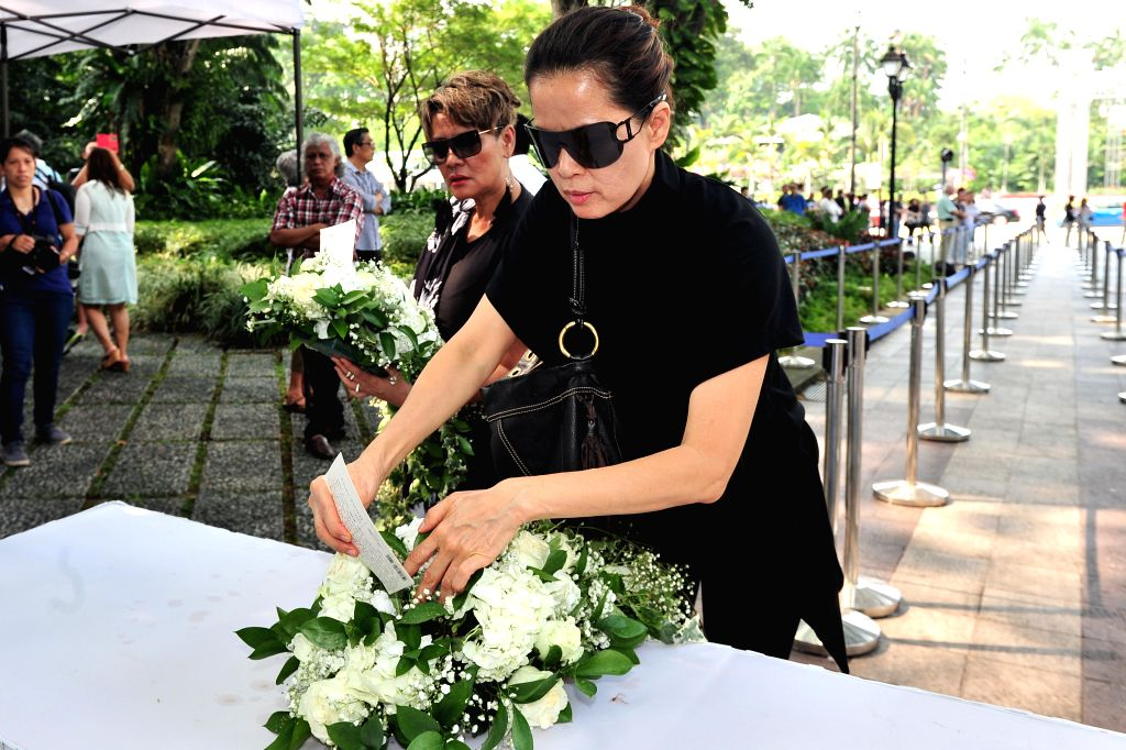 A woman lays flowers and a condolence card while paying tribute to the Singapore's founding Prime Minister Lee Kuan Yew outside Singapore's Istana, March 23, ...