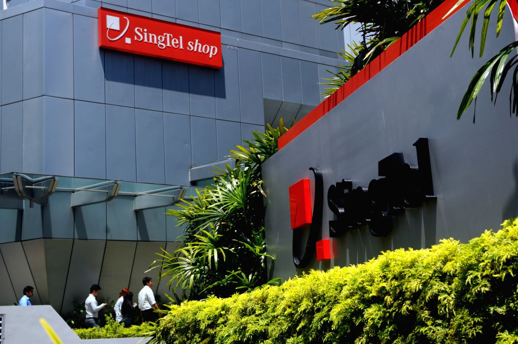 Pedestrians walk past the SingTel building in Singapore's Orchard Road area, on May 15, 2014. SingTel said on Wednesday that its performance of the financial year .