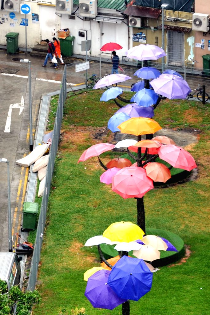 SINGAPORE, Oct. 7, 2016 - People holding umbrellas walk in the rain in Singapore's Little India, Oct. 7, 2016.