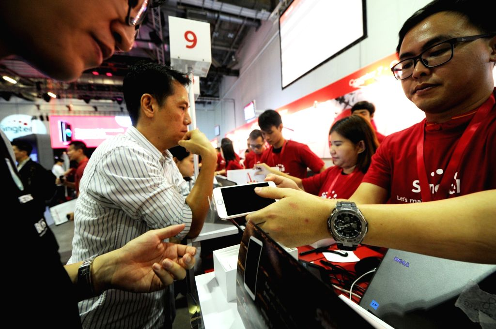 SINGAPORE, Sept. 16, 2016 - Customers checks his new iPhone during the Singtel Apple iPhone 7 launch event held in Singapore's Marina Bay Sands Expo on Sept. 16, 2016. The Apple iPhone 7 smart phone ...