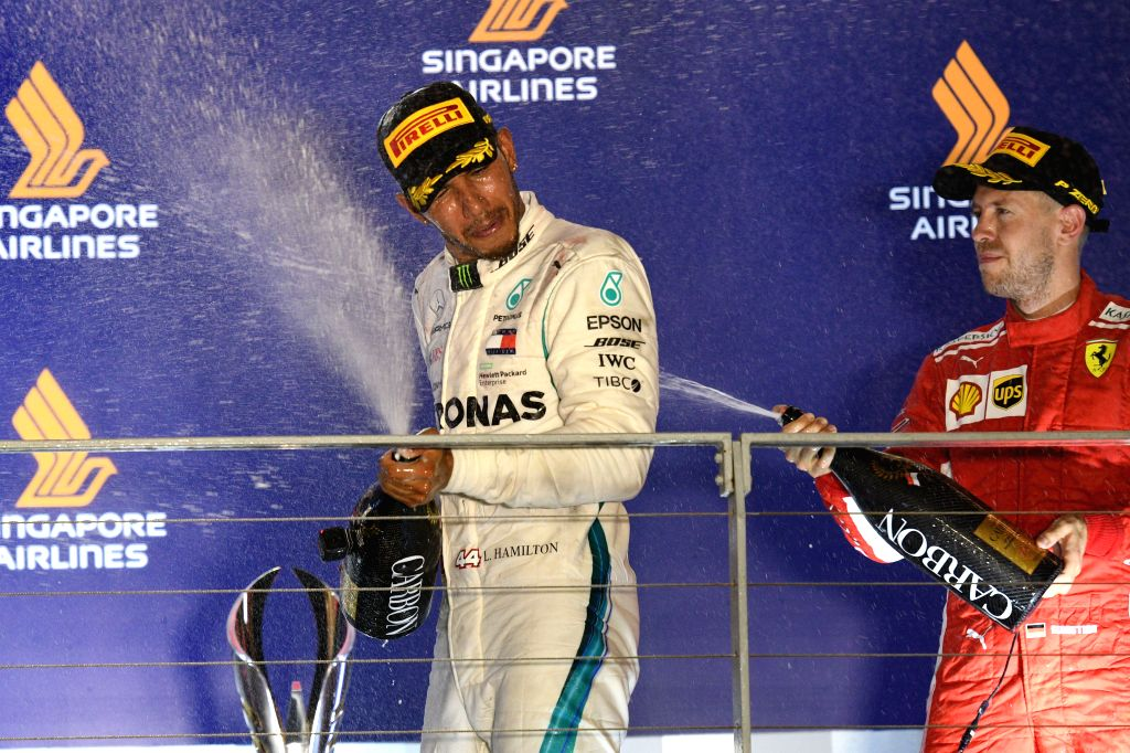SINGAPORE, Sept. 16, 2018 - First-placed Mercedes' driver Lewis Hamilton (L) of Britain celebrates during the awarding ceremony of the 2018 Singapore Formula One Grand Prix held at the Marina Bay ...