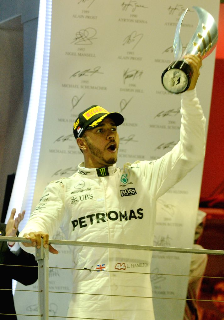 SINGAPORE, Sept. 17, 2017 - Mercedes' British driver Lewis Hamilton celebrates with the trophy on the podium after winning the Formula One Singapore Grand Prix in Singapore on Sept. 17, 2017.