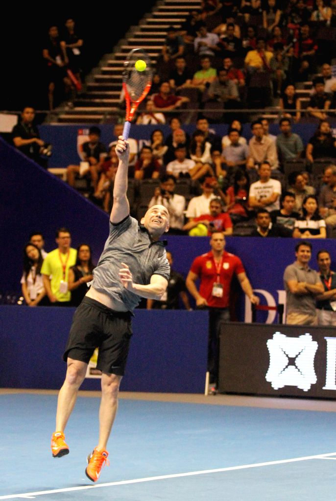 Tennis legend Andre Agassi hits a return during the first International Premier Tennis League (IPTL) at the Singapore Indoor Stadium, Dec. 2, 2014. The star-driven IPTL was founded in 2013