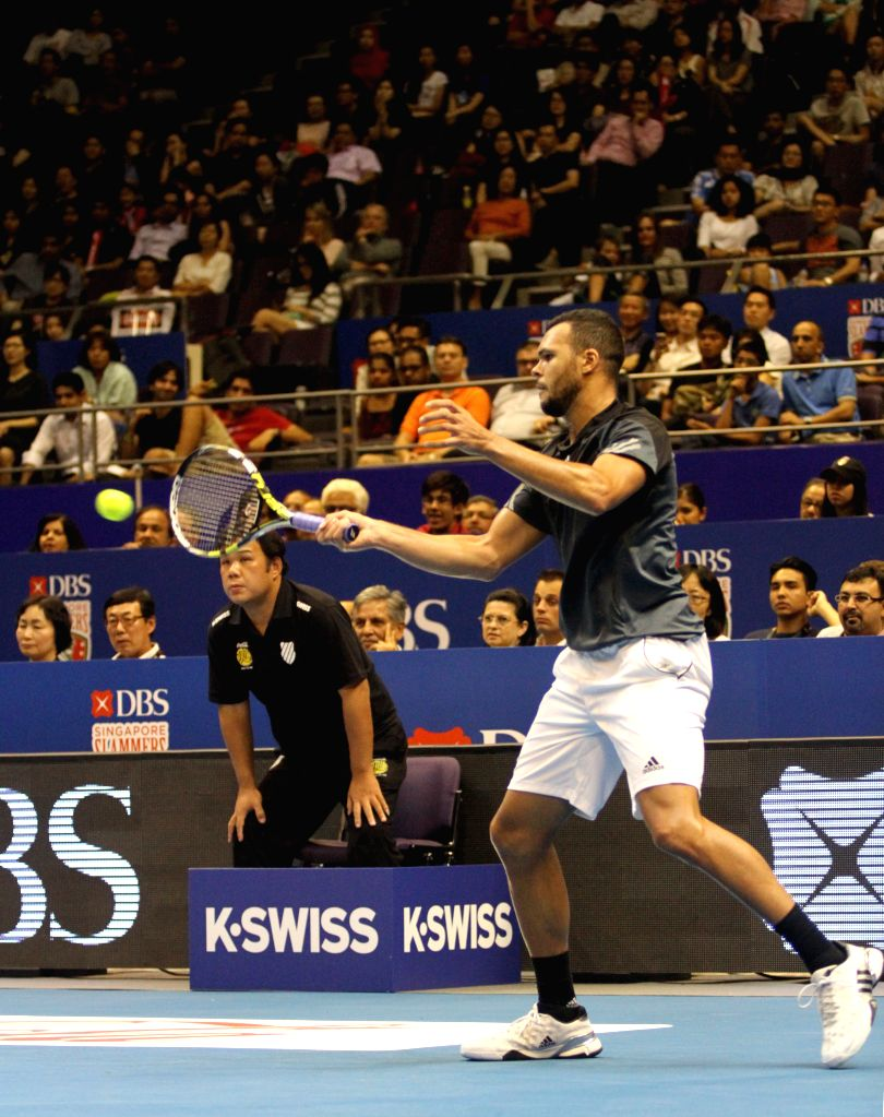 Tennis player Jo-Wilfried Tsonga hits a return during the first International Premier Tennis League (IPTL) at the Singapore Indoor Stadium, Dec. 2, 2014. The star-driven IPTL was founded ..