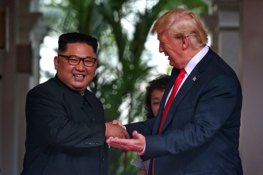 :Singapore: U.S. President Donald Trump and North Korean leader Kim Jong-un head for the negotiating table during their historic summit at the Capella Hotel in Singapore on June 12, 2018, in this ...
