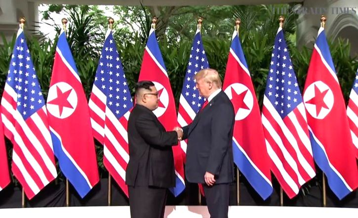 Singapore: U.S. President Donald Trump (R) shakes hands with North Korean leader Kim Jong-un ahead of their historic summit at the Capella Hotel in Singapore on June 12, 2018, in this photo captured from the website of The Strait Times. (Yonhap/IANS)
