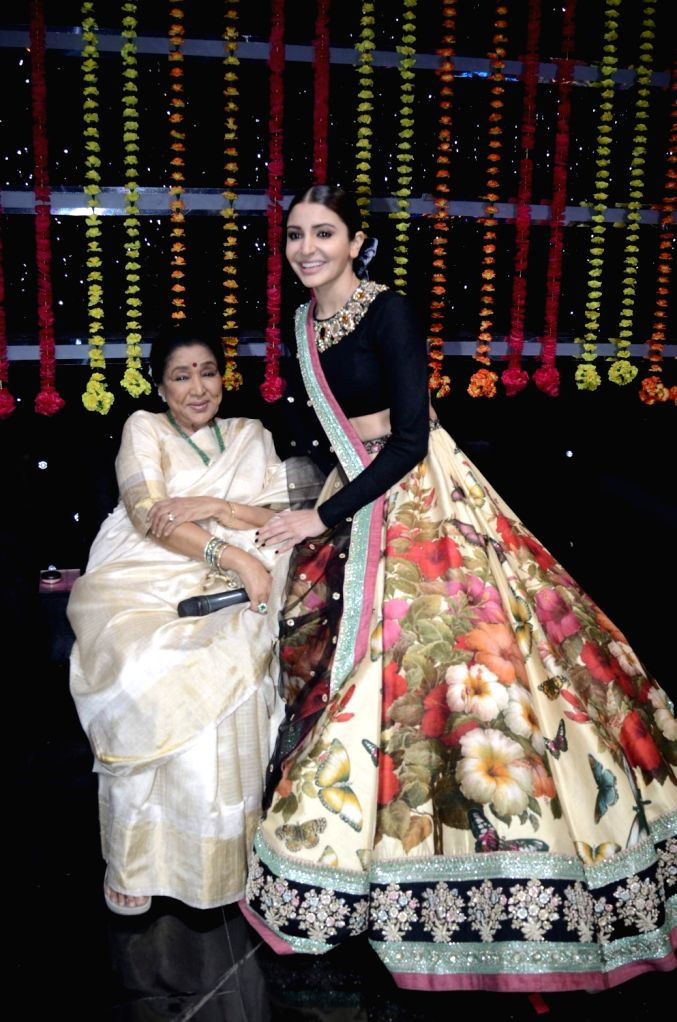 Singer Asha Bhosle and actress Anushka Sharma performs at the finale stage of TV reality show 'The Voice India' in Mumbai on March 12, 2017. - Anushka Sharma and Asha Bhosle