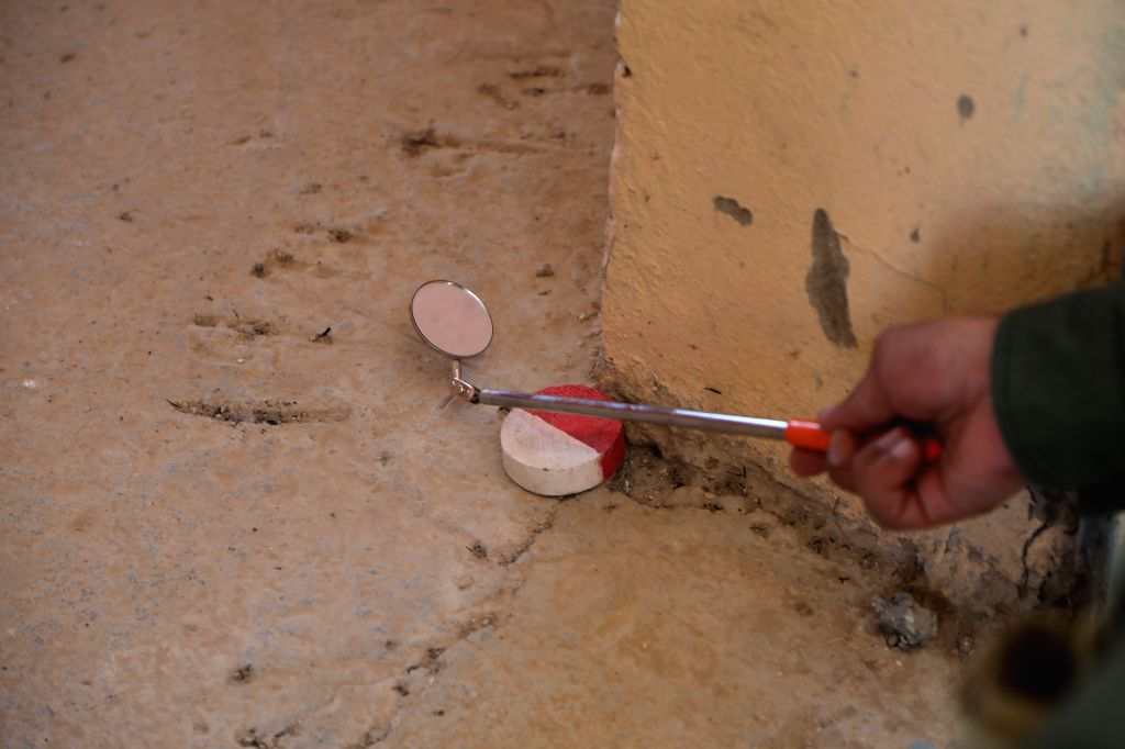SINJAR (IRAQ), Aug. 10, 2019 Photo taken on July 4, 2019 shows a searcher exploring blind spots with a mirror to clear explosive hazards from a school on the edges of Sinjar, Iraq. After ...