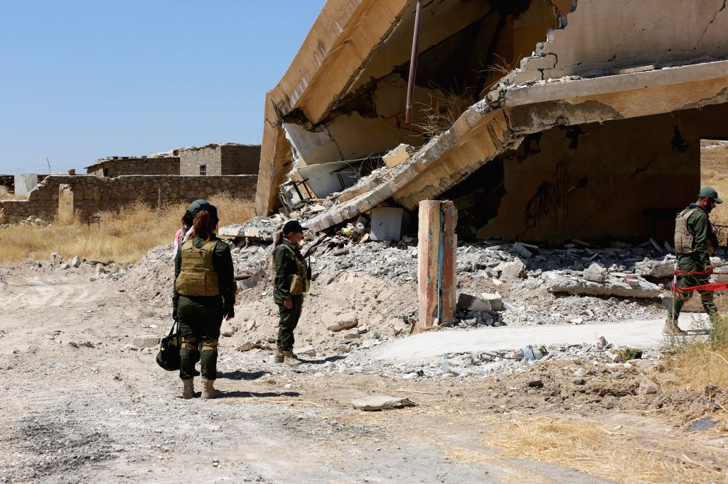SINJAR (IRAQ), Aug. 10, 2019 Photo taken on July 4, 2019 shows members of a Yazidi search team working to clear explosive hazards from a school on the edges of Sinjar, Iraq. After five ...