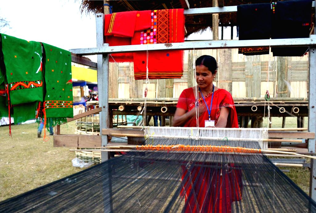A tribal woman from Mishing community weaving cloth at the Desang Brahmaputra festival at Desangmukh in Sivasagar district of Assam on Jan 3, 2015.