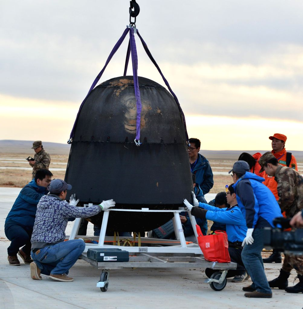 SIZIWANG BANNER, April 18, 2016 - Scientific personnel work at the landing area of the re-entry capsule of China's first retrievable microgravity satellite SJ-10 in Siziwang Banner, north China's ...