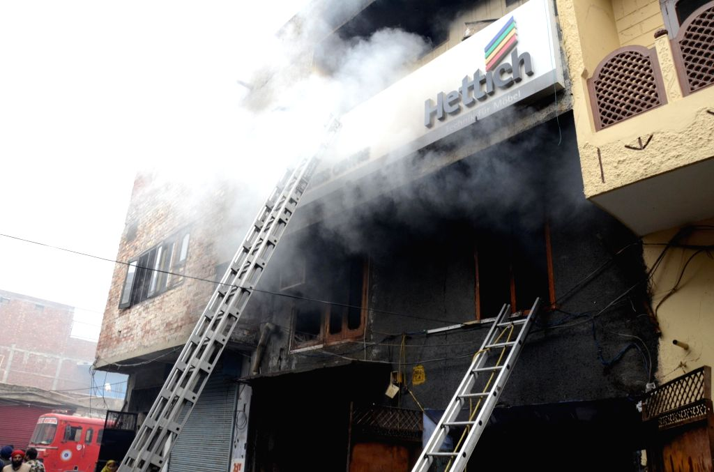 Smoke billows as firefighters douse a fire that broke out in a hardware store, in Amritsar on November 15, 2020.