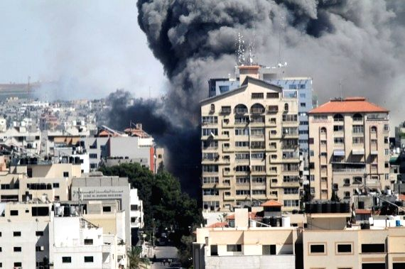 Smoke billows following an Israeli airstrike on Jala Tower, which housed offices of Al-Jazeera TV and Associated Press as well as residential apartments, in Gaza City, on May 15, 2021.