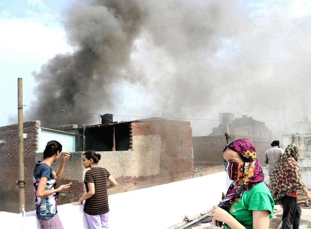 Smoke billows out of a building behind Gurudwara Sis Ganj Sahib after a fire broke out at Kinari Bazaar in New Delhi on June 8, 2017.