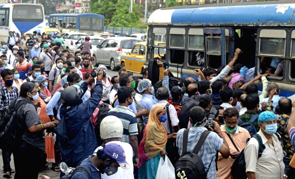 Social distancing goes for a toss as people rush to board a bus to their respective destinations during Unlock 3.0 amid COVID-19 pandemic, in Kolkata on Aug 6, 2020.