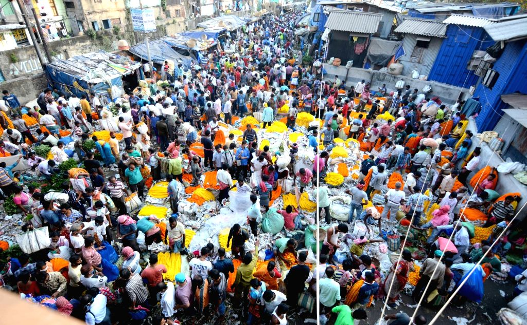 Social distancing norms go for a toss amid COVID-19 pandemic as people throng a wholesale flower market to shop for Kali Puja celebrations, in Kolkata on Nov 14, 2020.