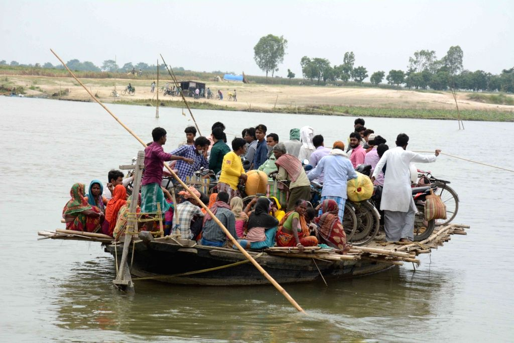 Social distancing orders being violated as people in Bihar's Katihar district sail through the waters of the Mahananda river on a crowded boat during the extended nationwide lockdown imposed ...