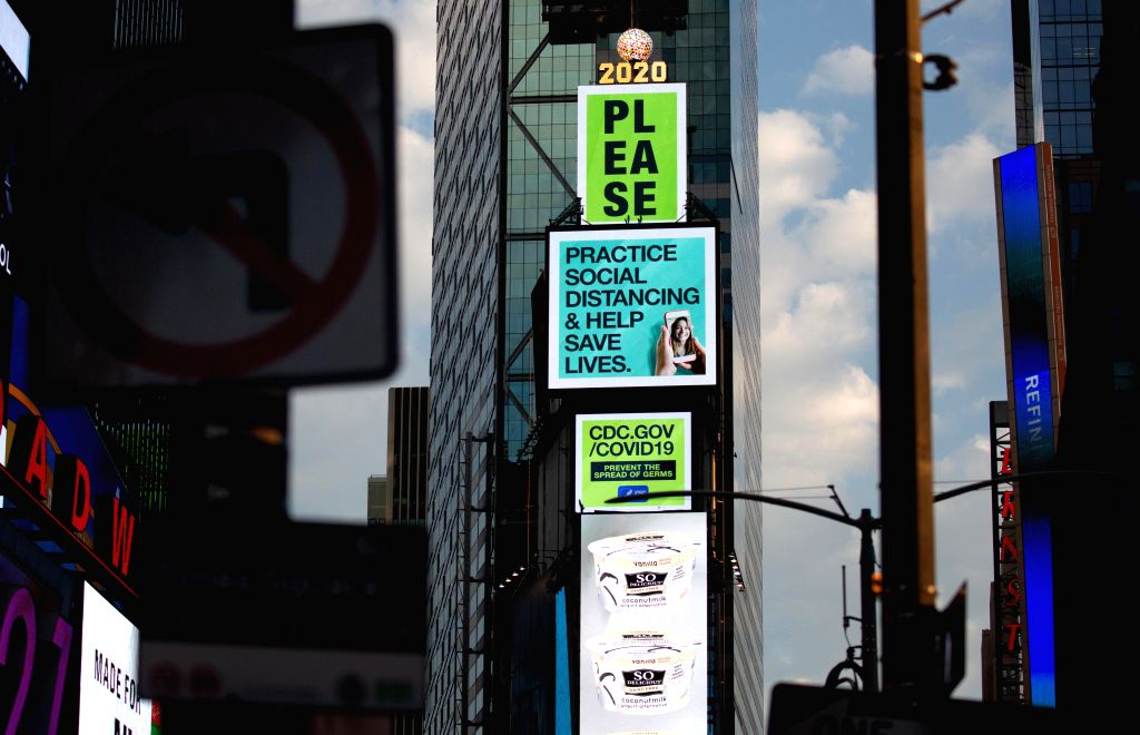 Social distancing signs are displayed on electronic billboards on Times Square in New York, the United States, June 25, 2020. The number of COVID-19 cases in the ...
