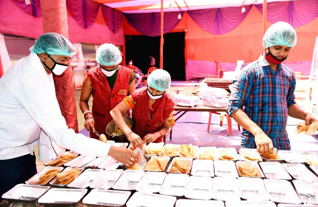 Social workers prepare food to be distributed among the poor, needy and homeless people during the 21-day nationwide lockdown imposed as a precautionary measure to contain the spread of ...