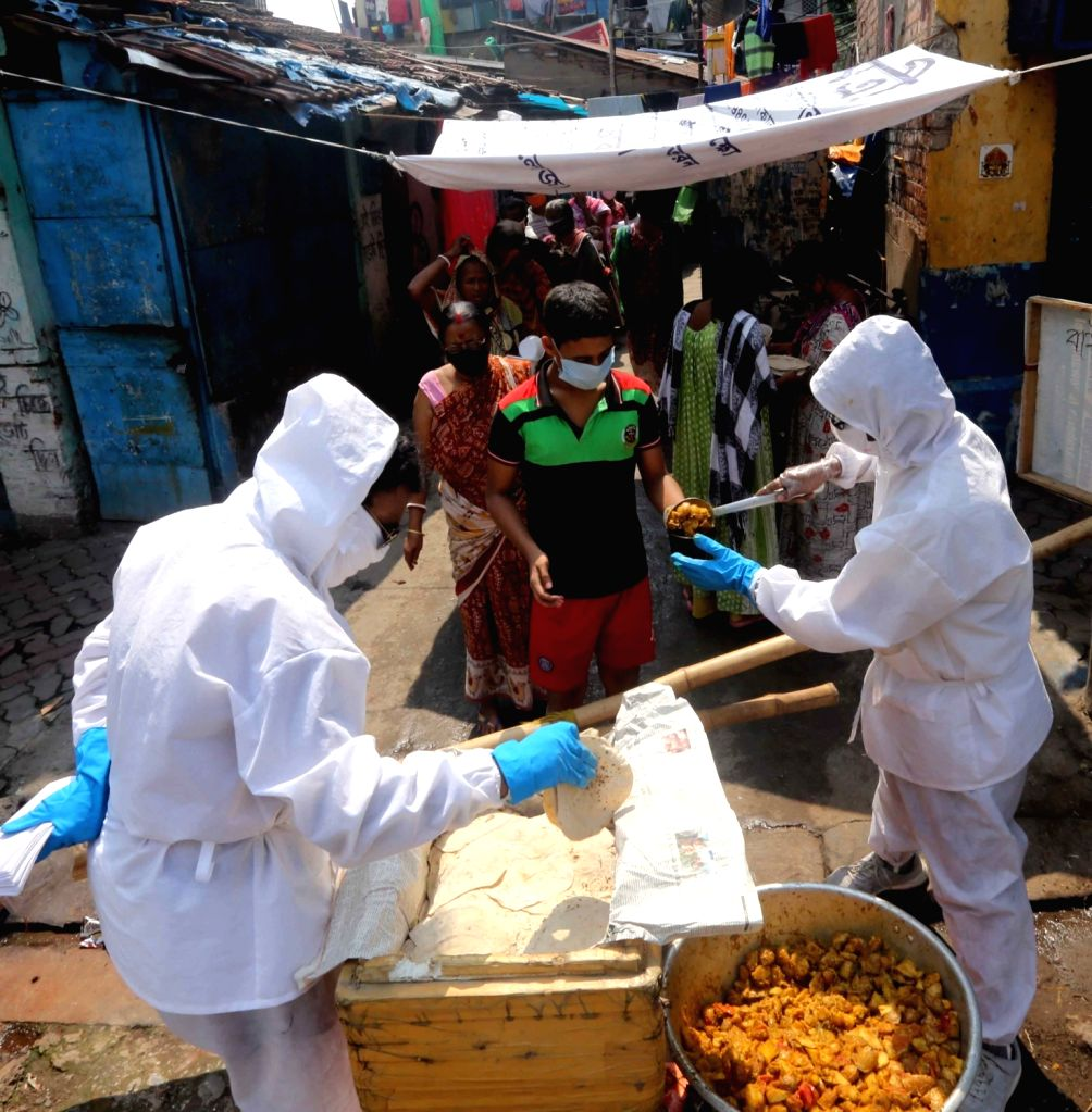 Social workers wearing Personal Protective Equioment (PPE) suits distribute food among the poor, needy and homeless in Kolkata  during the extended nationwide lockdown imposed to mitigate ...