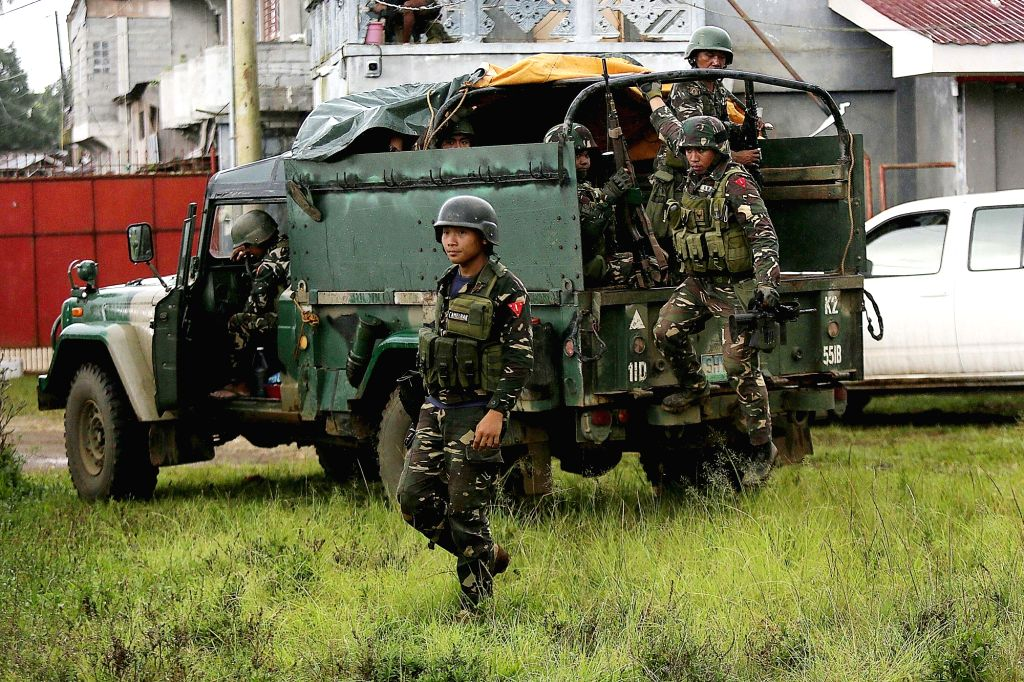 Soldiers disembark from a military truck as they search for residents still trapped in their homes in Marawi City in Lanao Del Sur Province, the ...