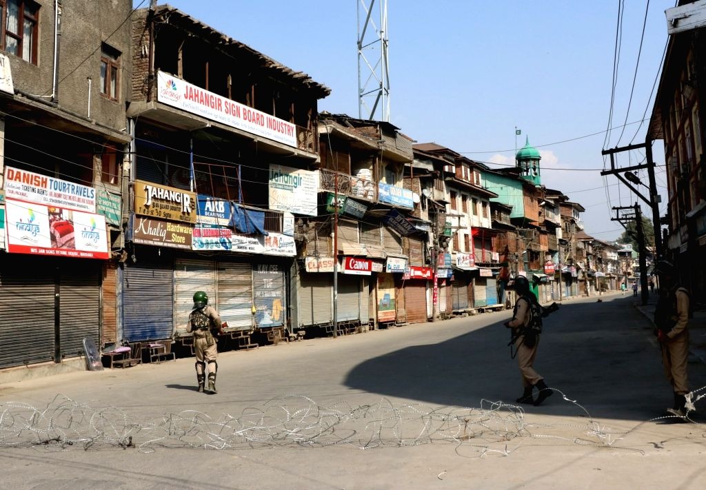 Soldiers man a street in Srinagar as authorities imposed curfew in parts of the city following clashes during the funeral of a 13-year-old boy who died of pellet injuries on Oct 8, 2016.