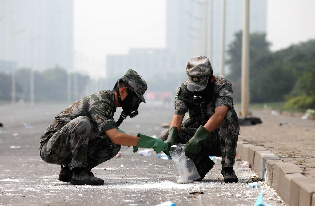 Soldiers of National Nuclear Biochemical Emergency Rescue Team take debris samples near the core area of explosion site in Tianjin, north China, Aug. 15, 2015. A ...