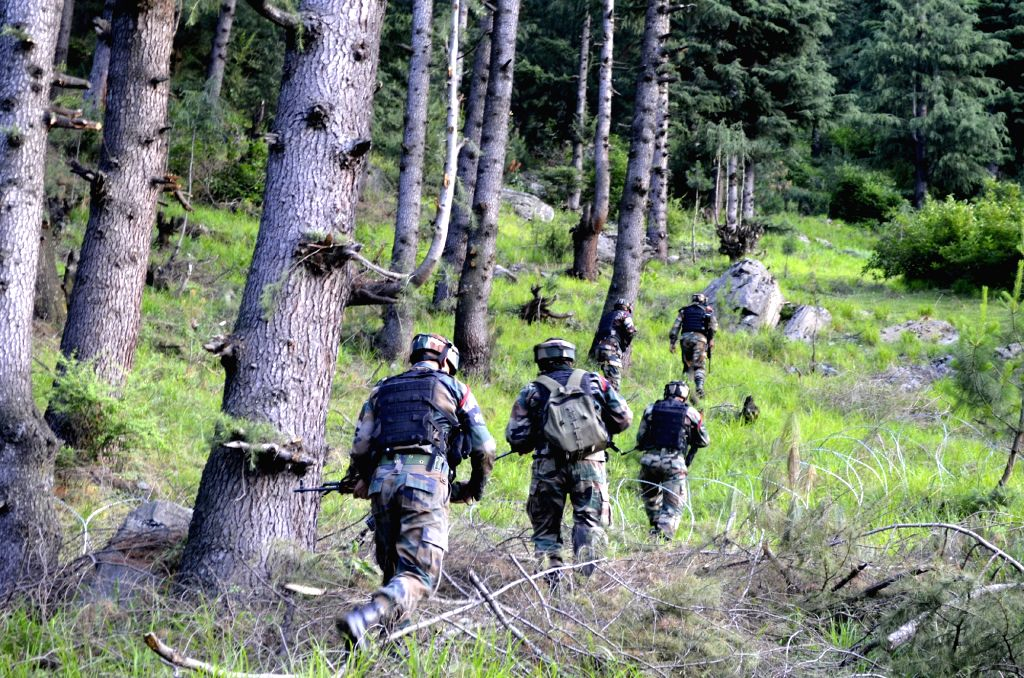 Soldiers take position during an operation in Uri of Baramulla.